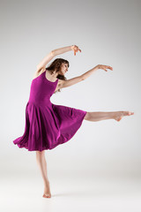 Young ballet dancer wearing purple dress over grey