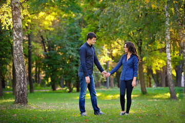 man and woman walking in the park