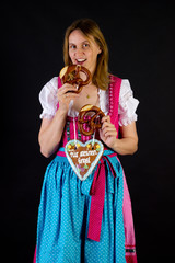 Woman in dirndl eating pretzel