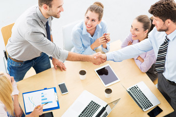 Business people shaking hands across table
