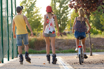 Group of friends with roller skates and bike riding in the park.