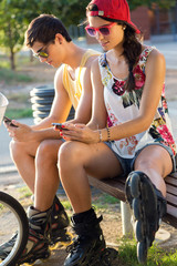 Group of friends texting with their smart phones in the park.