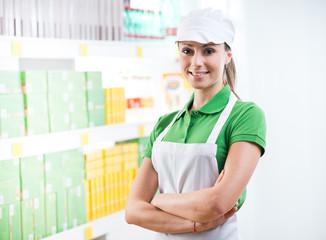 Smiling supermarket worker with shelf on background
