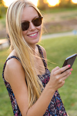 Young beautiful girl texting with her phone.