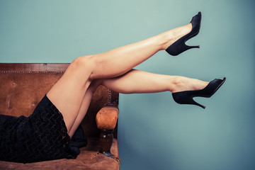Legs of a sexy young woman on sofa