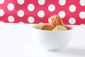 colourful french macaroons on polka dot background .
