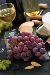 bunch of red grapes, assorted cheeses and appetizers, vertical