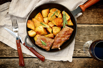 Beef steak in a pan with baked potatoes