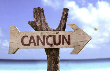 Cancun wooden sign with a beach on background