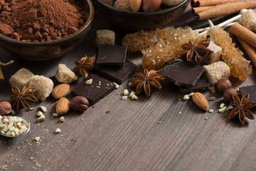 cocoa, chocolate, nuts and spices on wooden background