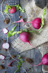 raw whole and sliced radishes on burlap on rustic wooden table