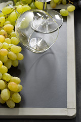 empty wine glass and grapes on a blackboard
