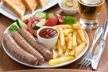 lunch with grilled sausages, French fries, vegetables and beer