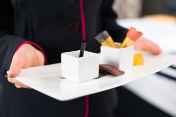 Roomservice serviert Dessert im Hotel Zimmer