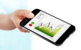 hand holding mobile phone with stock market chart isolated over