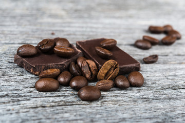 close up of coffee beans and chocolate on wooden background