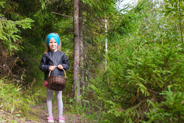 Little happy girl pick up mushrooms in autumn forest