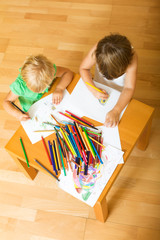 Siblings playing with pencils