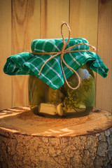 Jar pickled cucumbers wooden stump