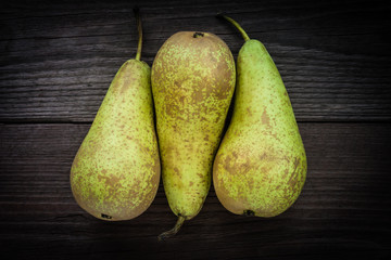three green pears on a wooden background