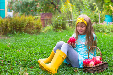 Little girl with basket of apples in autumn time
