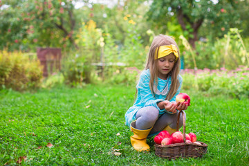 Adorable little girl with basket of red apples