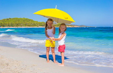 Little girls with big yellow umbrella walking on tropical beach