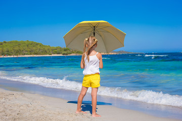 Rear view of little girl with big umbrella walking on tropical