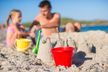 Father and adorable little daughter playing with beach toys