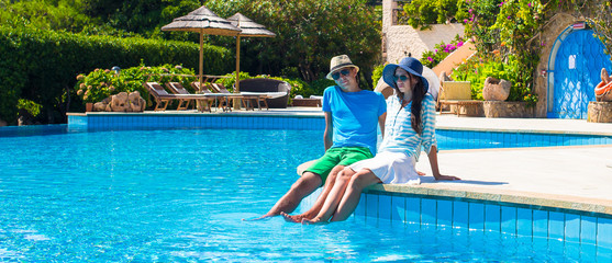 Lovely young romantic couple relaxing by swimming pool