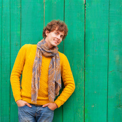 smiling curly man in yellow sweater and scarf on green wooden ba