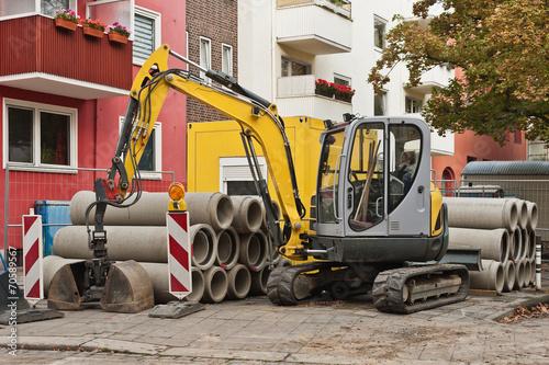 Bauarbeiten - Ein Minibagger steht vor Rohren aus Beton - 70589567