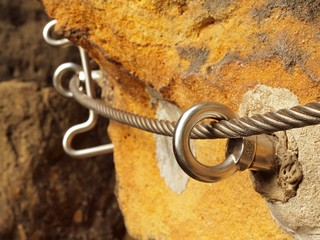 Detail of thin iron rope end anchored for climbers into rock