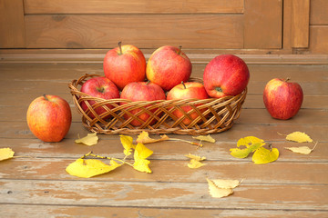 Still life with red apples in a wicker basket and yellow leaves