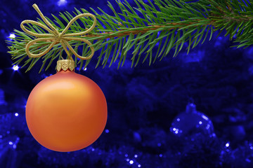 Christmas bauble and spruce branch on blue background