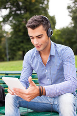 Man listening music in a city park