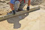 Worker screeding sand bed