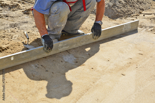 Worker screeding sand bed - 70593399