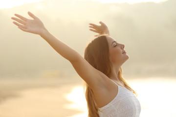 Relaxed woman breathing fresh air raising arms at sunrise