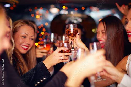 Leinwandbild Motiv beautiful women clinking glasses in limousine
