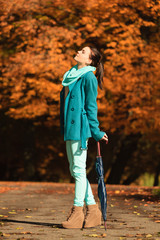 Girl walking with umbrella in autumnal park