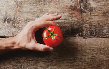 Mano con pomodoro su legno