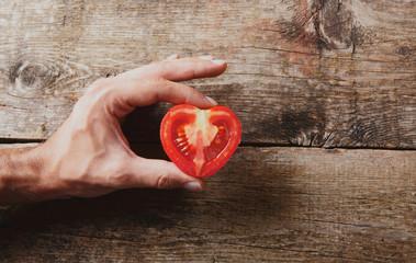 Mano con pomodoro tagliato su legno