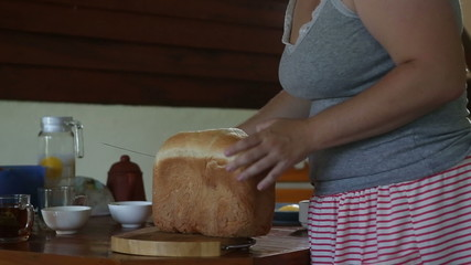 woman cuts off white bread crust