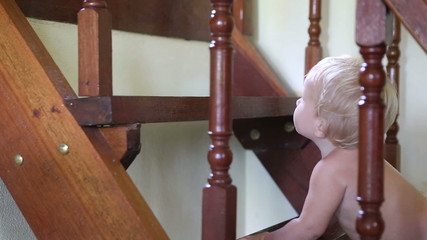 caucasian child tries to climb the stairs in house