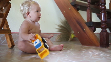 caucasian child plays with cars on the floor near the stairs