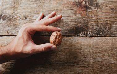 Mano con noce su legno