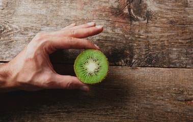 Mano con kiwi tagliato su bianco