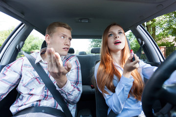Frivolous woman making up in car