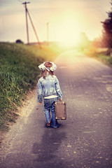 A little girl with an old suitcase sets off on a journey